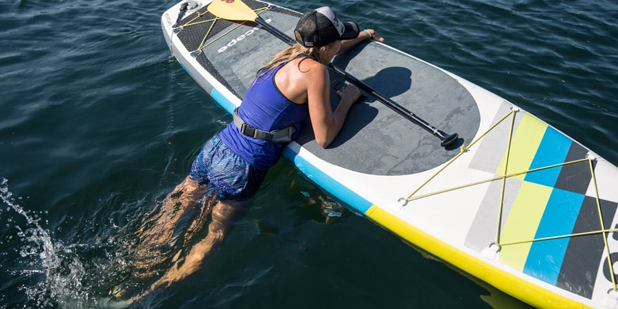 a stand up paddle boarder getting back on their board after falling off