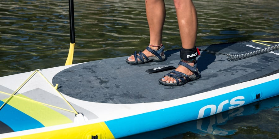 a stand up paddle boarder's stance for maintaining balance while on the board