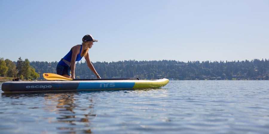 a stand up paddle boarder setting out on their paddling adventure in calm water and winds