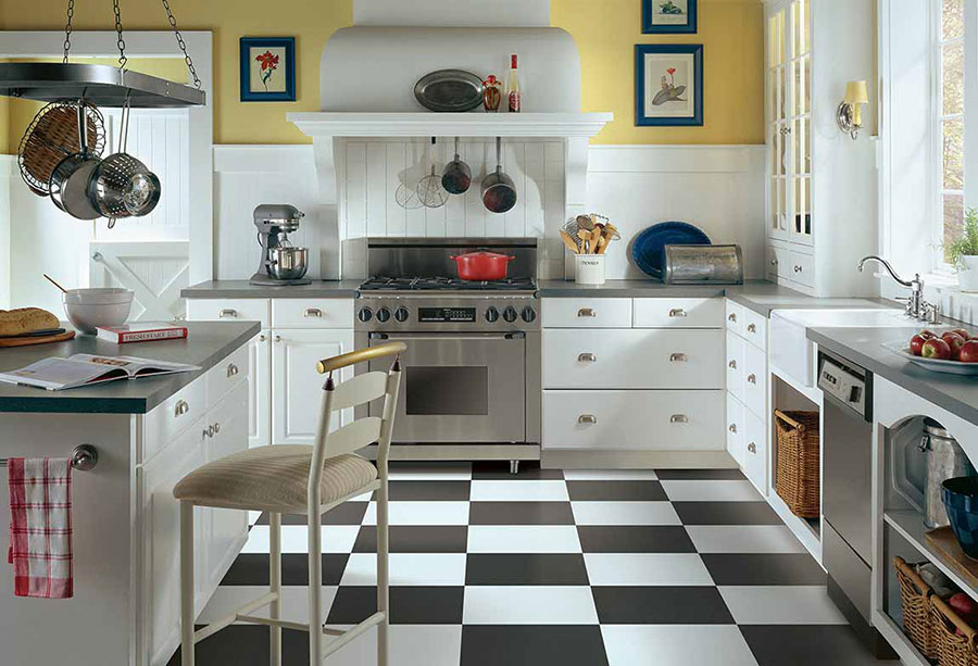 An older kitchen with a modern makeover to provide a retro look with modern stainless steel appliances on checkerboard themed luxury vinyl tile floors.
