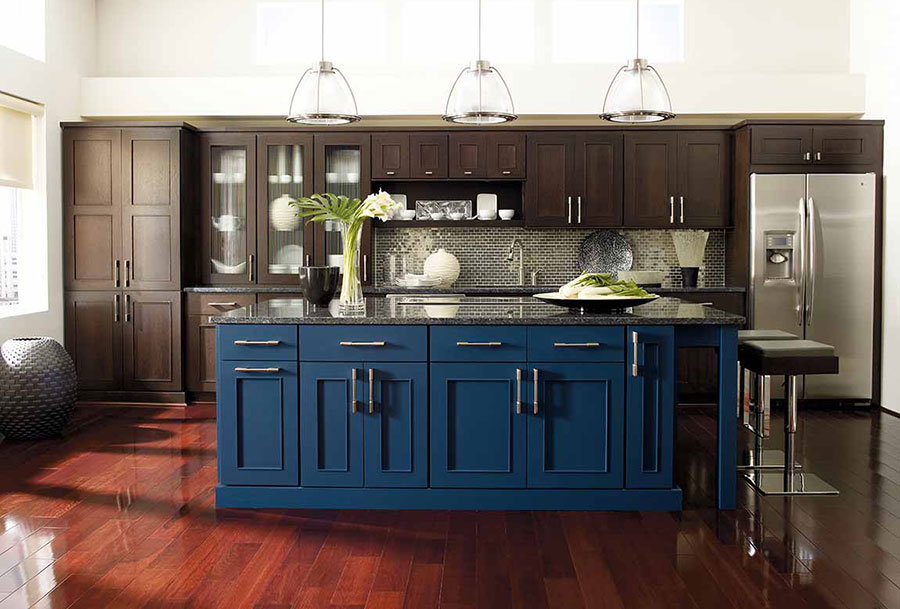 Modern kitchen with a large blue island and granite countertops, dark brown floor to ceiling cabinets, and stainless steel appliances on cherry stained wood floors.