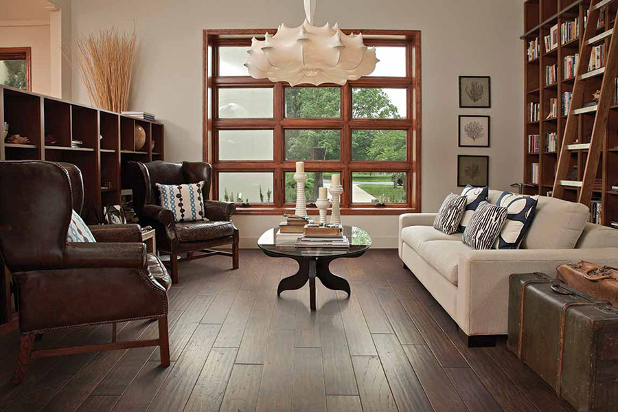 Living room decorated with plush dark brown leather chairs, a coffee table with books and tall candles, a sofa, antique suitcases, and a built-in bookshelf on dark brown engineered floors.